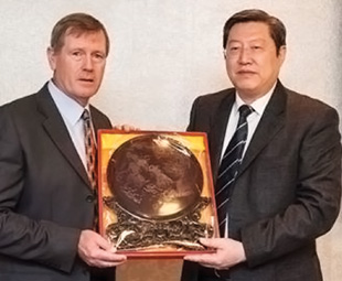 Vice Governor Zhang Jian Guo presenting a gift to Dave King, executive chairman of MICROmega, during his visit to the company's head office in Sandton, Johannesburg.