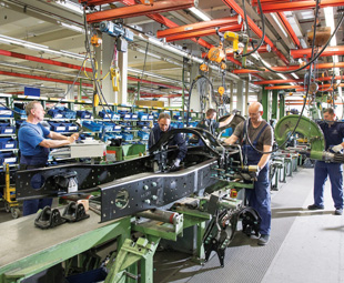 Workers assemble a truck chassis at the Mercedes-Benz Wörth plant.