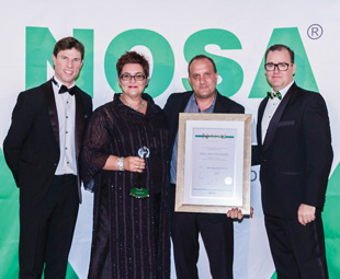 Carina Brink, DEKRA HSE manager, and Christopher Mơörsner, DEKRA operations manager, collect DEKRA's award from Nosa CEO Duncan Carlisle (far left) and MicroMega CEO Greg Morris (far right).